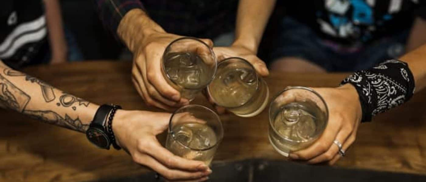 overhead-vie-friends-holding-glass-cocktails_23-2147883679